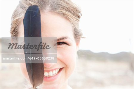 Smiling woman playing with feather Stock Photo - Premium Royalty-Free, Image code: 649-05658238