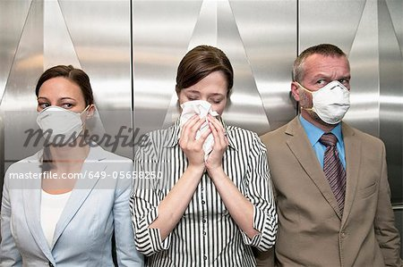 Woman coughing around others in elevator Stock Photo - Premium Royalty-Free, Image code: 649-05658250