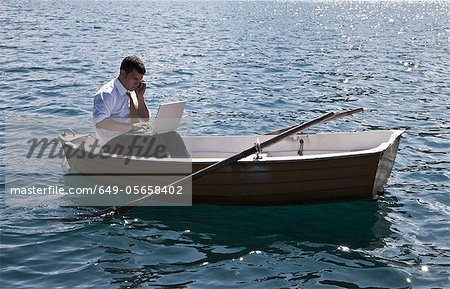 Businessman working in rowboat Stock Photo - Premium Royalty-Free, Image code: 649-05658402