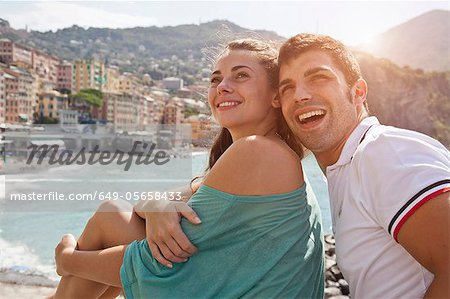 Couple sitting on stone wall by ocean Stock Photo - Premium Royalty-Free, Image code: 649-05658433