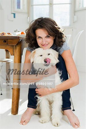 Woman hugging dog in kitchen Stock Photo - Premium Royalty-Free, Image code: 649-05800987