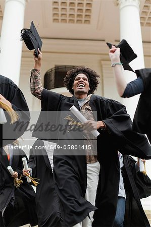 Graduates cheering on campus Stock Photo - Premium Royalty-Free, Image code: 649-05801415