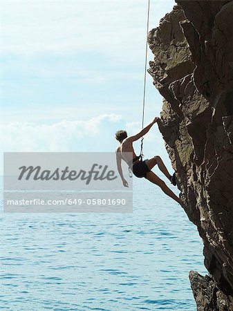 Rock climber rappelling down rock face Stock Photo - Premium Royalty-Free, Image code: 649-05801690