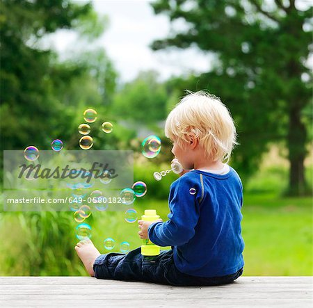 Boy blowing bubbles on porch Stock Photo - Premium Royalty-Free, Image code: 649-05801821