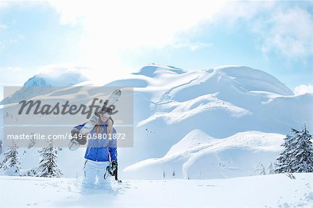 Man carrying snowboard in snow Stock Photo - Premium Royalty-Free, Image code: 649-05801872