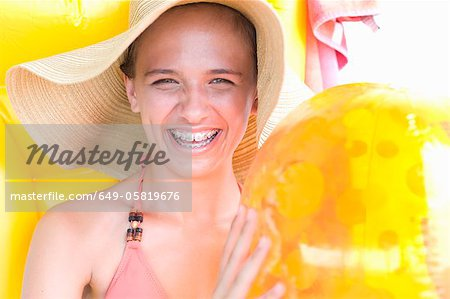 Teenage girl in braces wearing sunhat Stock Photo - Premium Royalty-Free, Image code: 649-05819676