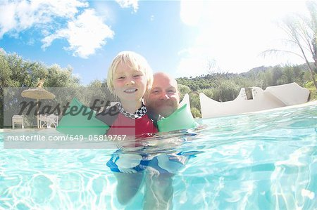 Father and son playing in pool Stock Photo - Premium Royalty-Free, Image code: 649-05819767