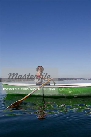 Woman rowing boat in still lake Stock Photo - Premium Royalty-Free, Image code: 649-05819834
