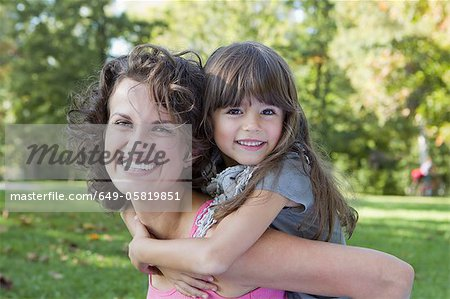 Mother carrying daughter outdoors Stock Photo - Premium Royalty-Free, Image code: 649-05819851