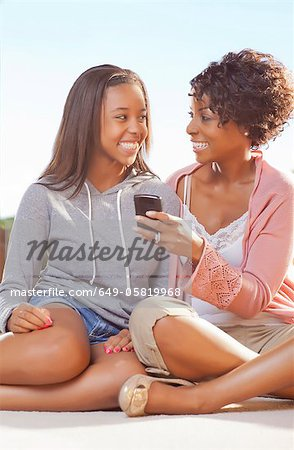 Mother and daughter using cell phone Stock Photo - Premium Royalty-Free, Image code: 649-05819968