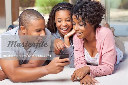 Smiling family using cell phone together Stock Photo - Premium Royalty-Free, Image code: 649-05819974