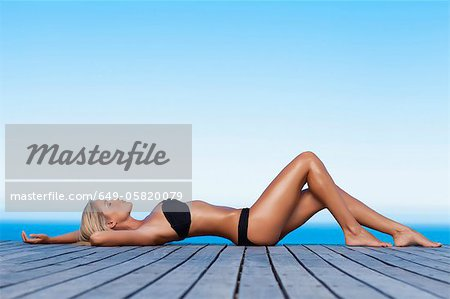 Woman sunbathing on wooden pier Stock Photo - Premium Royalty-Free, Image code: 649-05820079