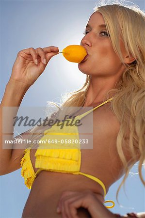 Smiling woman eating popsicle outdoors Stock Photo - Premium Royalty-Free, Image code: 649-05820233