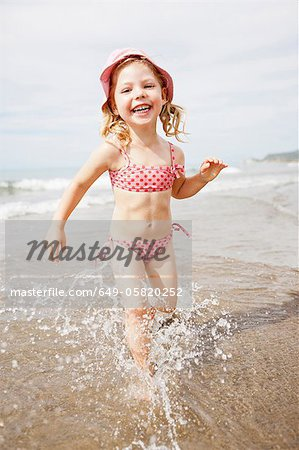 Smiling girl playing in waves on beach Stock Photo - Premium Royalty-Free, Image code: 649-05820252