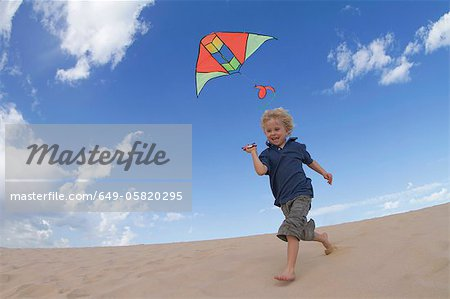 Boy flying kite on sand dune Stock Photo - Premium Royalty-Free, Image code: 649-05820295