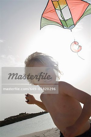 Smiling boy flying kite on beach Stock Photo - Premium Royalty-Free, Image code: 649-05820296