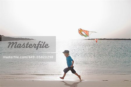 Boy flying kite on beach Stock Photo - Premium Royalty-Free, Image code: 649-05820298