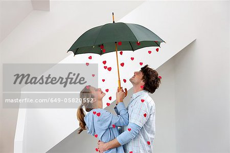 Couple standing under shower of hearts Stock Photo - Premium Royalty-Free, Image code: 649-05820552