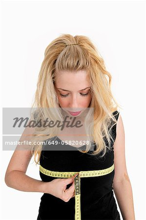 Woman measuring her bust Stock Photo - Premium Royalty-Free, Image code: 649-05820628