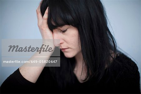Close up of woman clutching her head Stock Photo - Premium Royalty-Free, Image code: 649-05820647