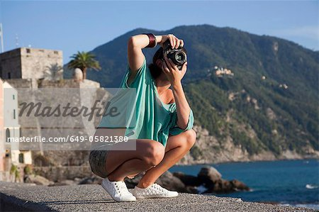 Woman taking pictures of coastline Stock Photo - Premium Royalty-Free, Image code: 649-05821380