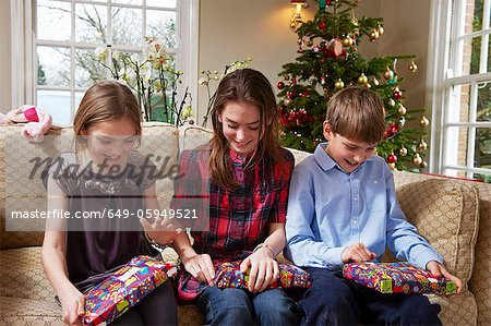 Children opening Christmas gifts Stock Photo - Premium Royalty-Free, Image code: 649-05949521