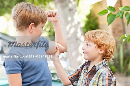 Boy feeling brothers biceps outdoors Stock Photo - Premium Royalty-Free, Image code: 649-05949581
