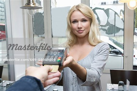 Hostess offering credit card machine Stock Photo - Premium Royalty-Free, Image code: 649-05949606