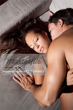 Couple kissing on sofa Stock Photo - Premium Royalty-Free, Image code: 649-05949652