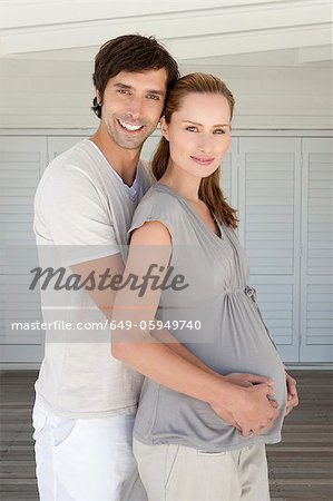 Man holding pregnant girlfriends belly Stock Photo - Premium Royalty-Free, Image code: 649-05949740