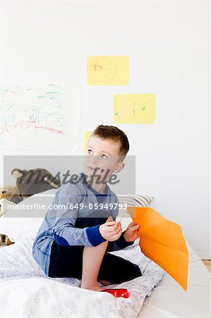 Boy holding drawing on bed Stock Photo - Premium Royalty-Free, Image code: 649-05949793
