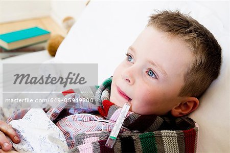 Boy with thermometer in mouth in bed Stock Photo - Premium Royalty-Free, Image code: 649-05949800