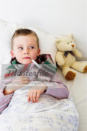 Boy with thermometer in mouth in bed Stock Photo - Premium Royalty-Free, Image code: 649-05949801