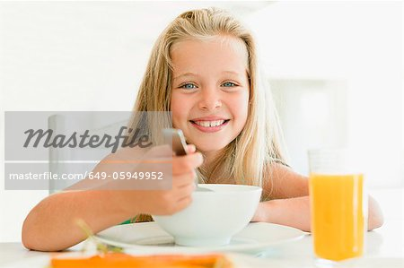 Girl eating cereal at breakfast table Stock Photo - Premium Royalty-Free, Image code: 649-05949952
