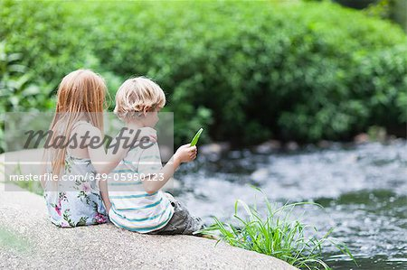 Children sitting on rock together Stock Photo - Premium Royalty-Free, Image code: 649-05950123
