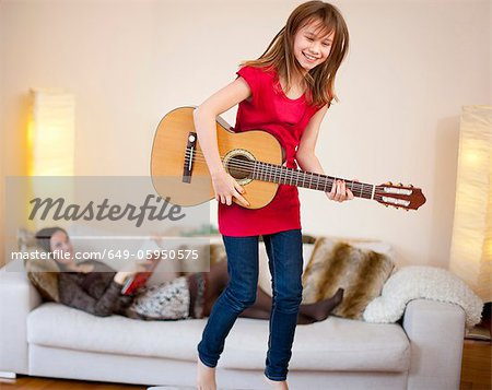 Girl playing guitar in living room Stock Photo - Premium Royalty-Free, Image code: 649-05950575