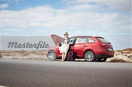 Woman with broken down car on rural road Stock Photo - Premium Royalty-Free, Image code: 649-05950788