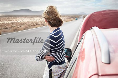 Woman with broken down car on rural road Stock Photo - Premium Royalty-Free, Image code: 649-05950789