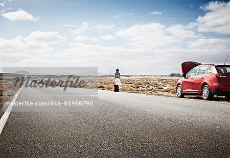 Woman with broken down car on rural road Stock Photo - Premium Royalty-Free, Image code: 649-05950790