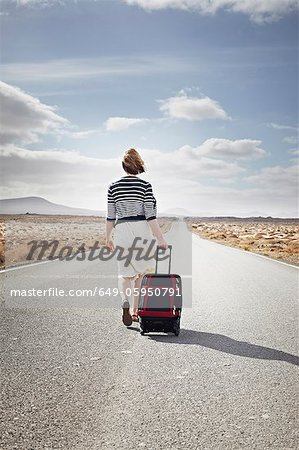 Woman rolling luggage on rural road