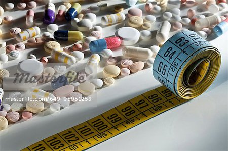 Scattered pills and measuring tape Stock Photo - Premium Royalty-Free, Image code: 649-05951259