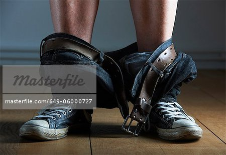 Mans jeans fallen around his ankles Stock Photo - Premium Royalty-Free, Image code: 649-06000727
