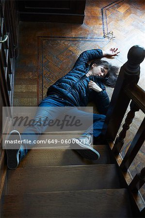 Teenage boy laying at foot of stairs Stock Photo - Premium Royalty-Free, Image code: 649-06000732