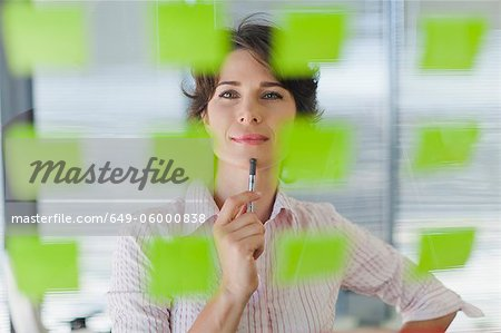 Businesswoman reading sticky notes Stock Photo - Premium Royalty-Free, Image code: 649-06000838