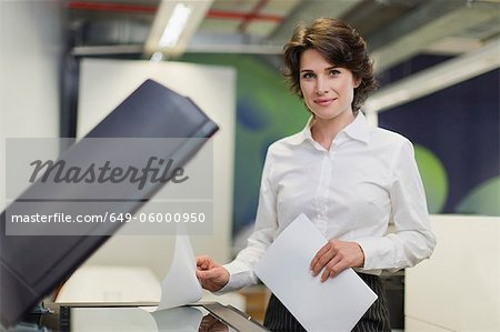 Businesswoman making copies in office Stock Photo - Premium Royalty-Free, Image code: 649-06000950