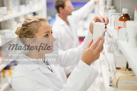 Pharmacists browsing medicines on shelf Stock Photo - Premium Royalty-Free, Image code: 649-06001025