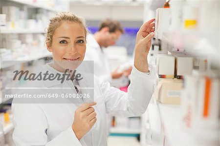 Pharmacists browsing medicines on shelf Stock Photo - Premium Royalty-Free, Image code: 649-06001026