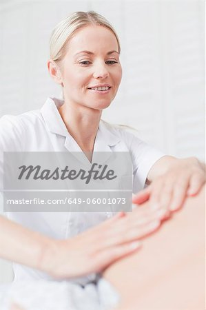 Doctor examining pregnant womans belly Stock Photo - Premium Royalty-Free, Image code: 649-06001073