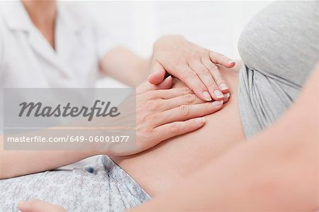 Doctor examining pregnant womans belly Stock Photo - Premium Royalty-Free, Image code: 649-06001077