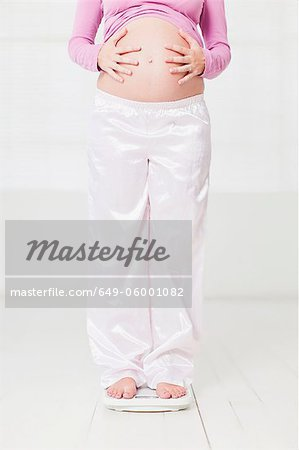 Pregnant woman weighing herself Stock Photo - Premium Royalty-Free, Image code: 649-06001082